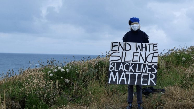 photo of a woman at the lakeshore, holding a sign that reads: End white silence, black lives matter