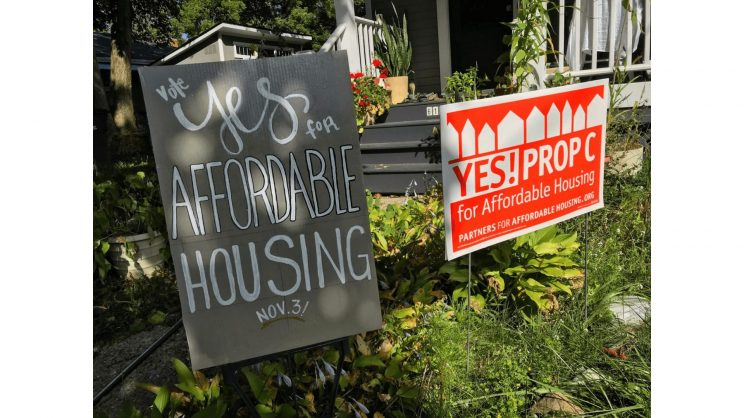 Photo shows two yard signs supporting Proposal C for affordable housing